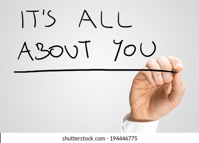 Male hand writing phrase It's all about you on virtual screen.