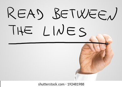 Male hand writing phrase Read between the lines on virtual screen.