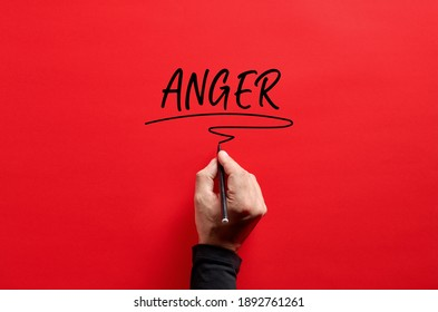 Male hand writing the word anger on red background. Anger management concept.