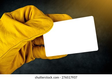 Male Hand in Yellow Leather Construction Working Protective Gloves Holding Horizontal Blank Business Card with Rounded Corners.