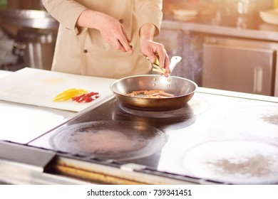 Male hands adding pepper to frying pan. Chef at professional kitchen cooking vegetables.