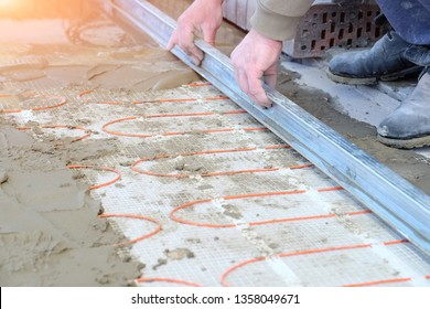 male hands with aluminium hand screed pouring concrete slab on heating cable for installing comfortable and adjustable warm floor
