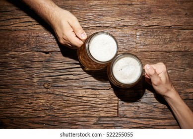 Male hands with beer mug on an old wooden table