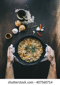 Male hands with bowl of fried rice with pork over the aged wooden table. Top view. Vintage style