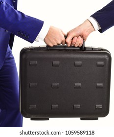 Male hands carry briefcase for exchange. Successful business deal concept. Male hands in suits hold briefcase. Handover of case or bribe in hands of business partners, isolated on white background.