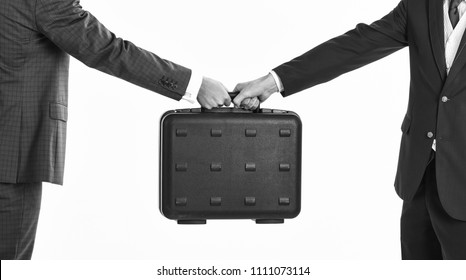 Male hands carry briefcase for exchange. Male hands in suits hold black briefcase. Business exchange concept. Handover of case in hands of business partners, isolated on white background.