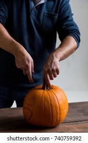 Male hands carving pumpkin