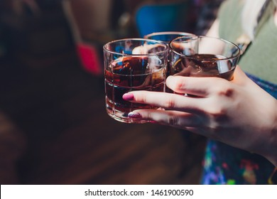 Male hands cheer with glasses of shot or liqueur. Friends drink shot or liqueur and cheers. Male hands cheer with alcohol on blurred bar background. Party and toast concept.