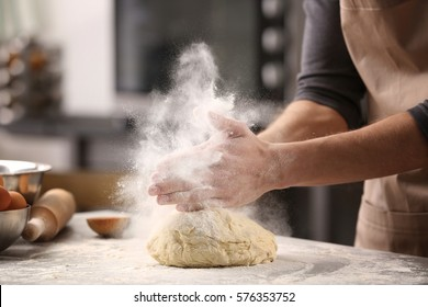 Male hands clapping and sprinkling white flour over dough on kitchen background