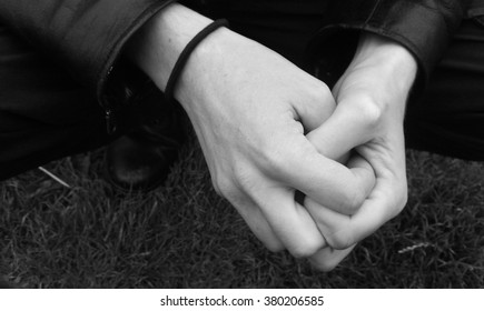 Male hands clasped together loosly.