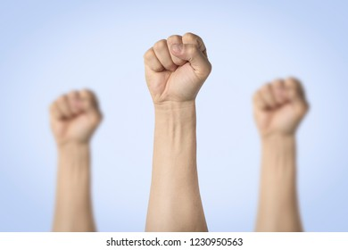 Male hands clenched into a fist and raised up on a blue background. Concept of power, rebellion, unity, revolution, riot