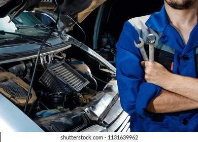 Male hands close-up with wrenches. The auto mechanic works in the garage. Repair service. Maintenance of the car, car repair.