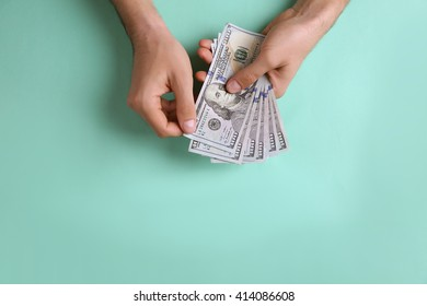 Male hands counting dollar banknotes on turquoise background
