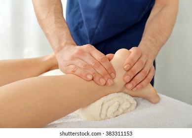 Male hands doing legs massage close-up
