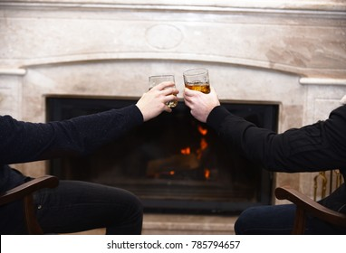 Male hands with drinks in glasses on fireplace background. Friends cheers with bourbon in glasses sitting by fire. Glasses with whisky in male hands. Hands clinking cognac glasses near the fireplace.