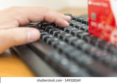 Male hands entering credit card information into a computer