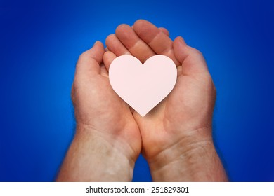 Male hands folded in a cup and holded aheart on a blue background