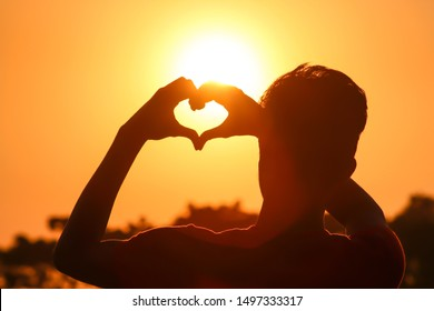 male hands in the form of heart against the sky pass sun beams.