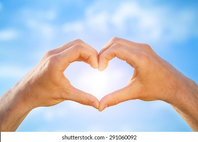 Male hands in the form of heart isolated on blue sky background. Sun is shining.