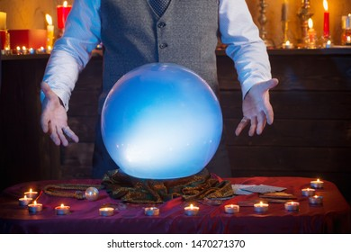 male hands of fortune teller with illuminated crystal ball