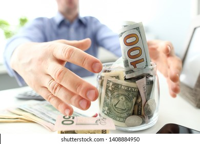 Male hands grabbing big fat jar full of US currency as greed gesture closeup
