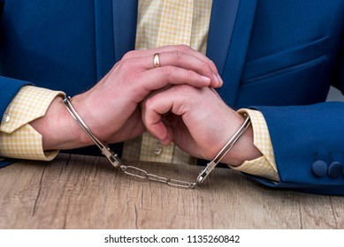 Male hands in handcuffs on wooden table