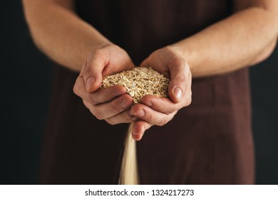 A male hands with a handful of oat flakes