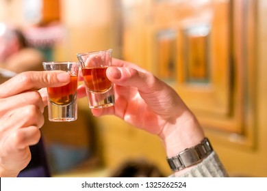 male hands having toast with shot glasses of grappa