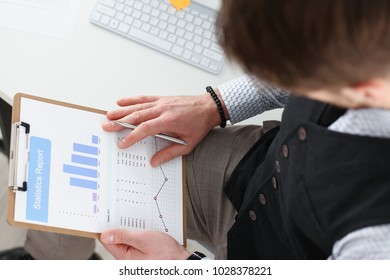 Male hands hold clipboard pad financial statistics