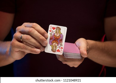 Male hands hold a deck of cards and show tricks. The photographer is the author of the design of playing cards, which is written in the release of the property.