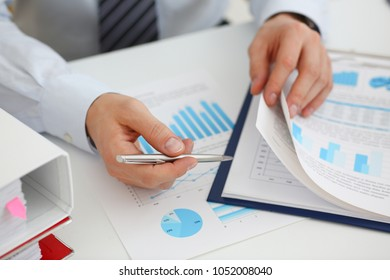 Male hands hold documents with financial statistics at office workspace closeup. White collar check money papers stock exchange market internal Revenue Service inspector earning list concept