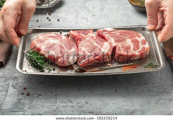 Male hands hold the iron tray with raw steaks close up