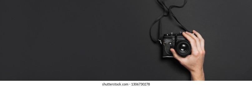 Male hands hold old vintage camera on black background top view flat lay with copy space. Concept for the photographer, old photographic equipment, minimalistic style long banner