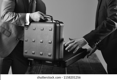 Male hands hold opened black briefcase on wooden table on dark background. Offer bribe concept. Businessmen offer illegal transaction or bribe.