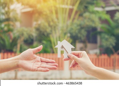 Male hands hold of paper house with key. Building, loan, housewarming, insurance, real estate or buying a new home concept. Vintage style.