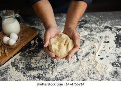 male hands hold raw dough on a wooden background. Milk and Raw Chicken Eggs