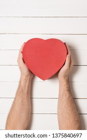 Male hands hold a red heart shaped box against the background of a white wooden table.