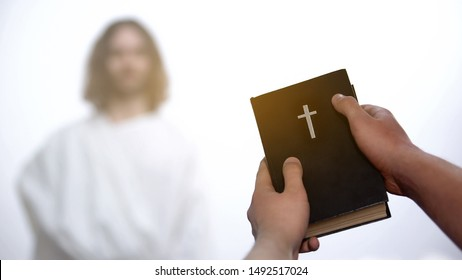 Male hands holding Bible, praying to appeared God on background, salvation