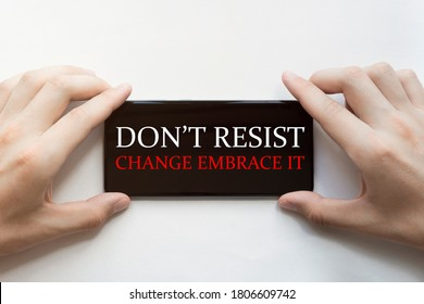 male hands are holding black phone with text Do Not Resist Change Embrace It on white background