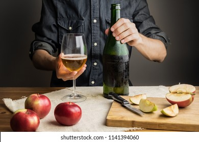 Male hands holding bottle of premium cider on rustic wood table. Beautiful ice cold bottle of apple wine, with ripe apples in background