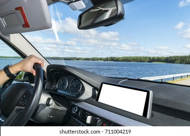Male hands holding car steering wheel. Hands on steering wheel of a car driving near the lake. Man driving a car inside cabin. Multimedia system isolated white blank screen. Copy space
