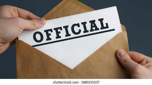 Male hands holding craft envelope with word OFFICIAL on blue background, communication concept