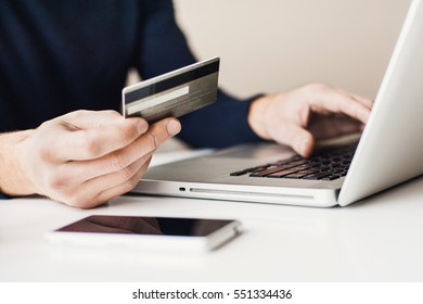 Male hands holding credit card and using laptop.  Businessman or entrepreneur working from home. Online shopping, e-commerce, internet banking, spending money, work from home concept