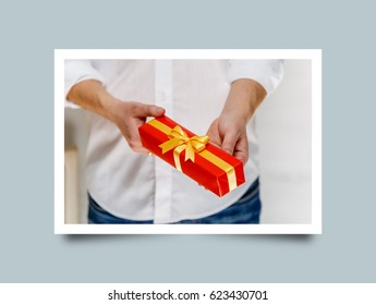 Male hands holding a gift box. Present wrapped with ribbon and bow. Christmas or birthday red package. Man in white shirt. Photo frame design with shadow.