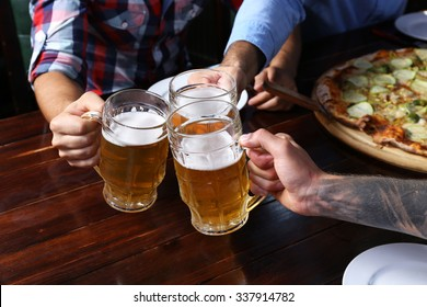 Male hands holding glasses with beer
