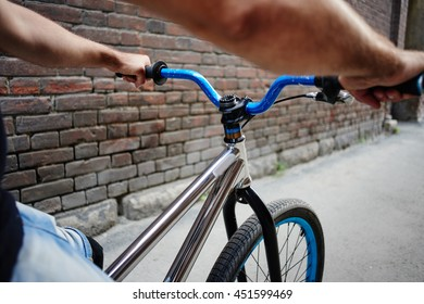 Male hands holding the handlebar of the bike near the wall of the red brick building