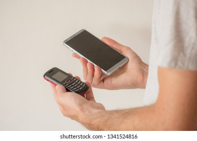 Male hands holding a new smart phone and an old cellphone, on white background. Planned obsolescence concept, technology development, history of communications, millenial devices
