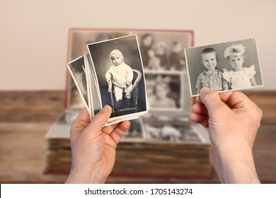male hands holding an old retro album with vintage monochrome photographs in sepia color 1964-1965, the concept of genialogy, memory of ancestors, family ties, childhood memories