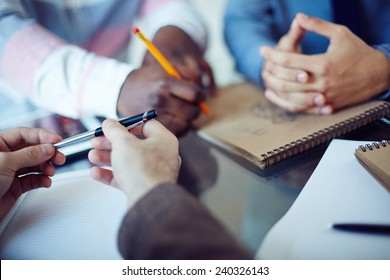 Male hands holding pen in working environment