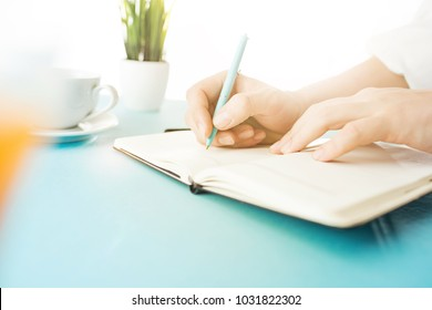 Male hands holding pen, writing. Side view on man on trendy color blue desk. Man and stilish workplace.